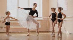 zdjęcie przedstawia baletnicę z dziecmi w sali tanecznej
