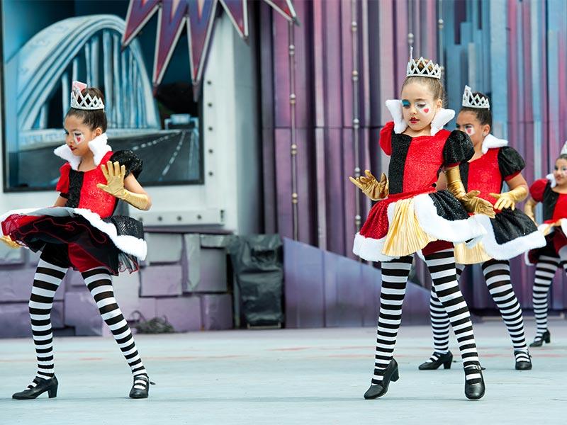 dzieci tańczą spektakl, mają kolorowe stroje