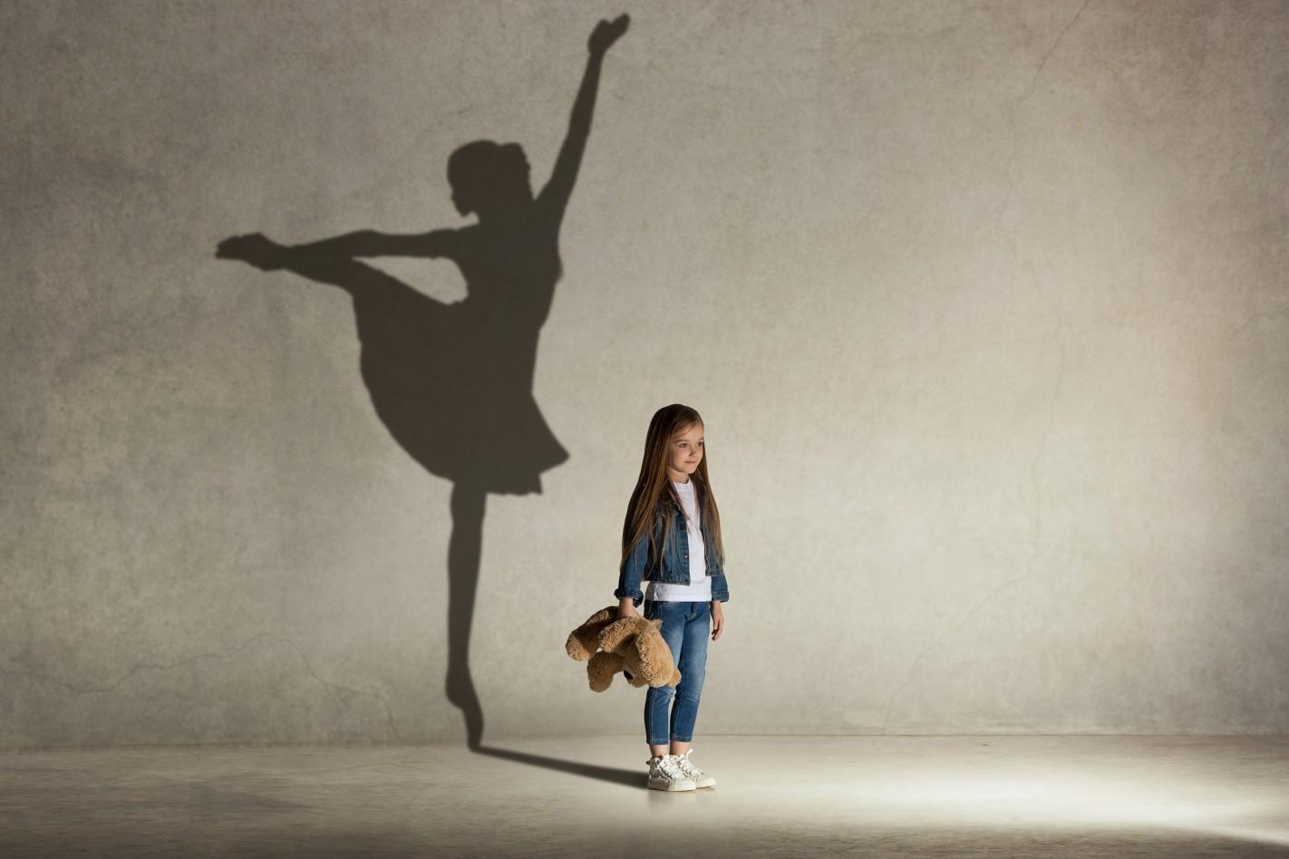 zdjęcie przedstawia dziewczynke trzymającą misia za którą jest cień tancerki - baletnicy
