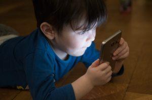 dziecko patrzy na ekran smartfona