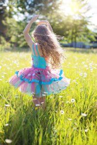 Dziewczynka tańczy na trawie
