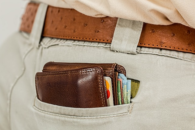 gruby portfel z kartami kredytowymi i dużą ilością gotówki w kieszeni spodni mężczyzny