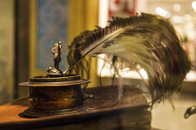 zdjęcie przestawia biurko na którym jest kałamarz z piórem