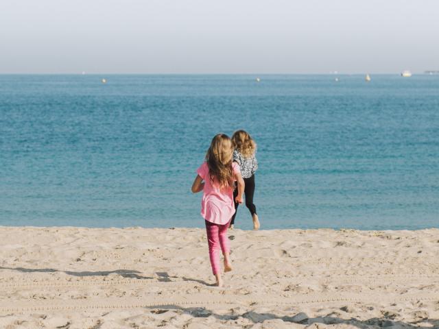 dziewczynki biegnące po plaży w letni dzień